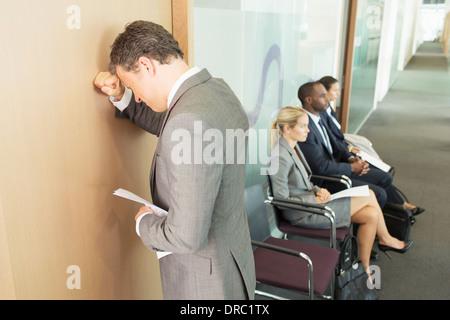 Businessman leaning on office door - Stock Photo