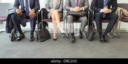Business people sitting in waiting area - Stock Photo