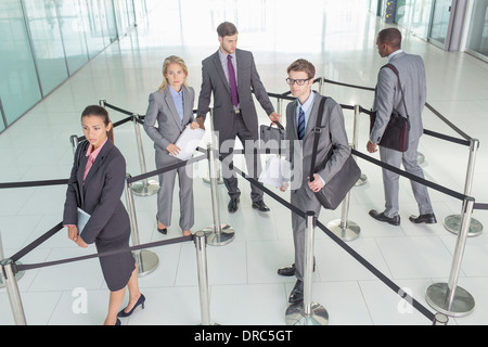 Business people standing in roped-off area - Stock Photo