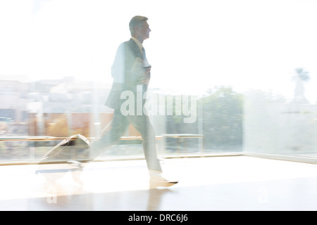 Businessman running in sunny airport - Stock Photo