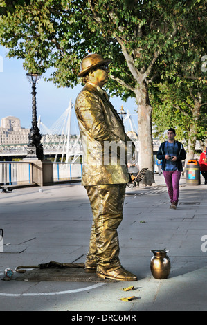 Gold human statue on the South Bank, London, England, UK - Stock Photo