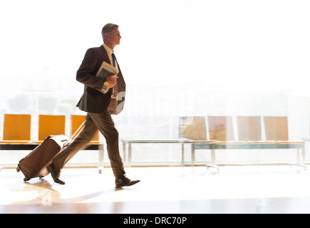 Businessman running with suitcase in airport corridor - Stock Photo