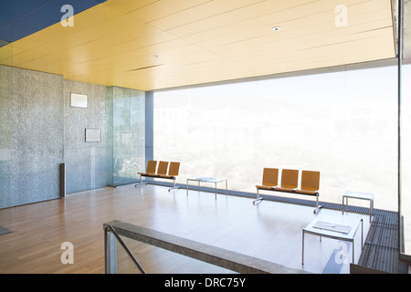 Chairs at window in empty lobby - Stock Photo