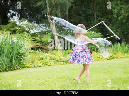 Girl making large bubbles in backyard - Stock Photo