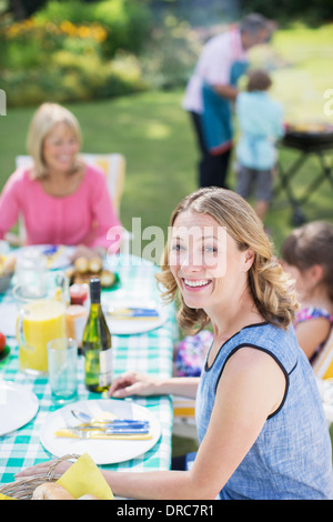 Woman smiling at table in backyard - Stock Photo