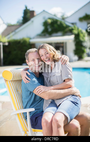 Couple sitting in lounge chair at poolside - Stock Photo