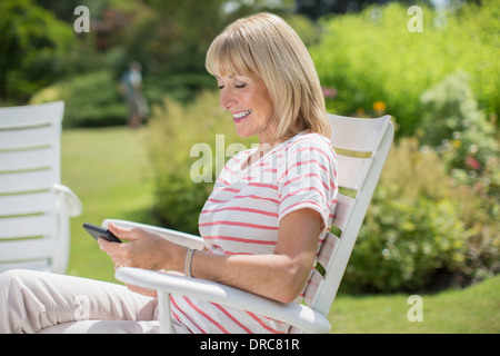 Woman using cell phone in garden - Stock Photo