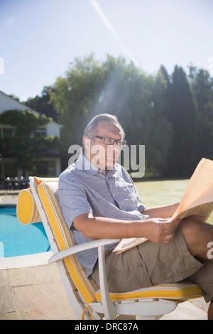 Man reading newspaper at poolside
