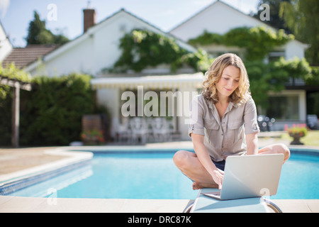 Woman using laptop on diving board at poolside - Stock Photo