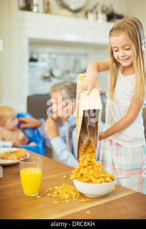 Girl pouring bowl cereal on breakfast table - Stock Photo