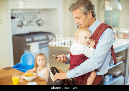 Father with baby packing bag for work - Stock Photo