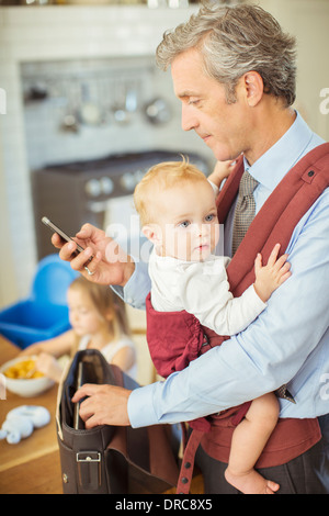 Father holding baby and checking cell phone - Stock Photo