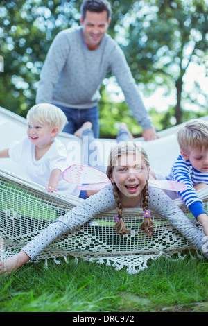 Father pushing children in hammock outdoors - Stock Photo