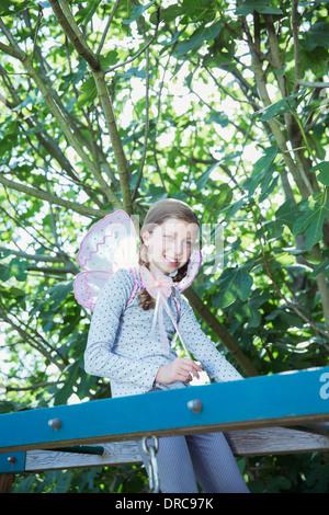 Girl smiling on monkey bars outdoors - Stock Photo