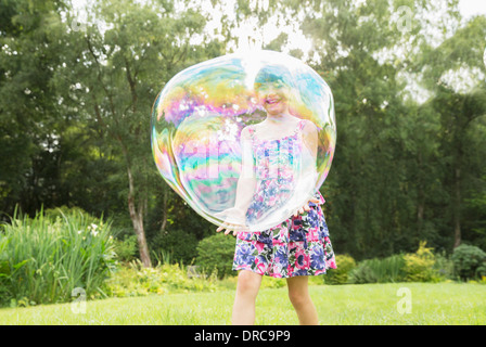 Father and daughter playing with large bubbles in backyard - Stock Photo