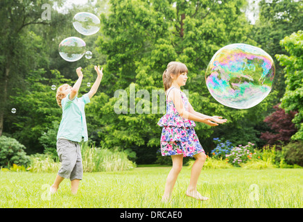 Children playing with bubbles outdoors - Stock Photo