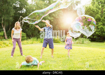 Family playing with large bubbles in backyard - Stock Photo