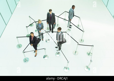 Business people waiting in roped off area - Stock Photo