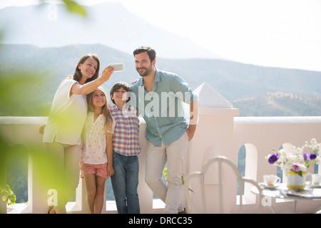 Family taking self-portrait on sunny balcony - Stock Photo