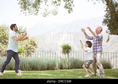 Multi-generation family playing volleyball in backyard - Stock Photo