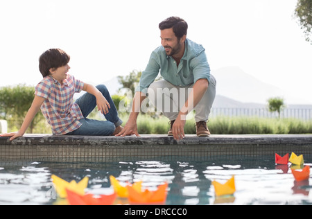Father and son watching origami boats in swimming pool - Stock Photo