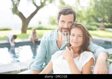 Couple relaxing at poolside Stock Photo