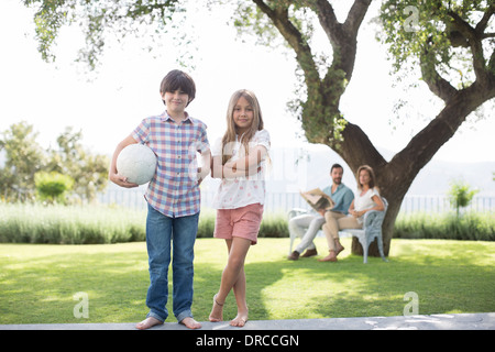 Brother and sister with volleyball in backyard - Stock Photo