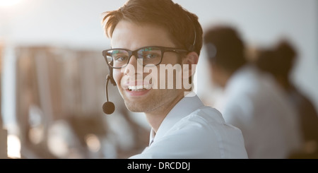 Businessman wearing headset in office - Stock Photo