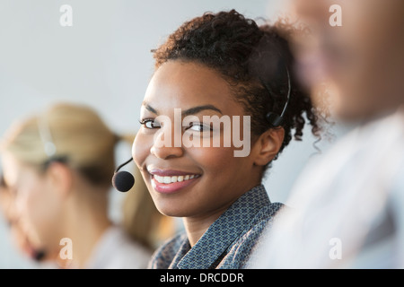 Businesswoman wearing headset in office - Stock Photo