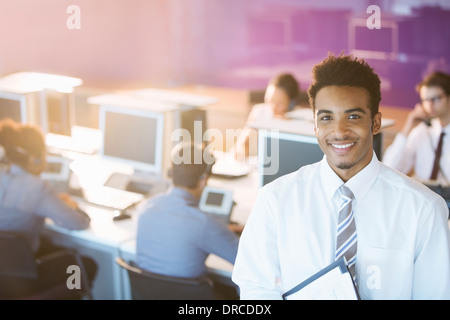 Businessman smiling in office - Stock Photo