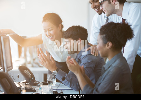 Business people cheering at computer in office - Stock Photo