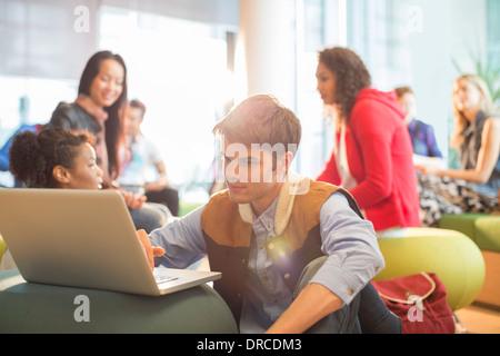 University student using laptop in lounge - Stock Photo