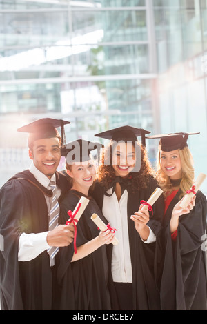 Smiling graduates holding diplomas - Stock Photo