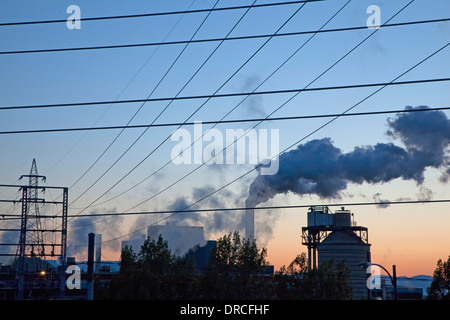 Silhouette of smoke emitting from factory at sunrise - Stock Photo