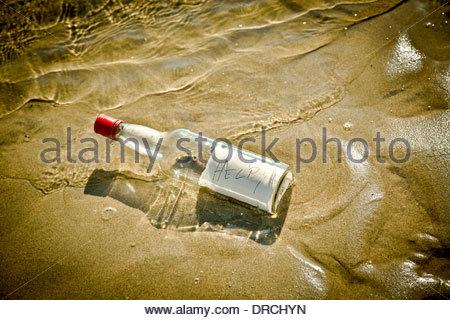 Bottle washed up on sandy beach - Stock Photo