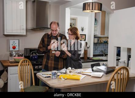 senior couple in kitchen with finances - Stock Photo