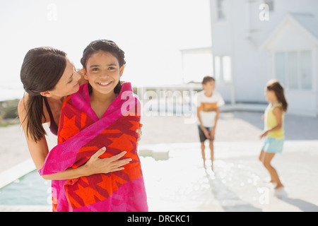 Mother wrapping daughter in towel at poolside Stock Photo