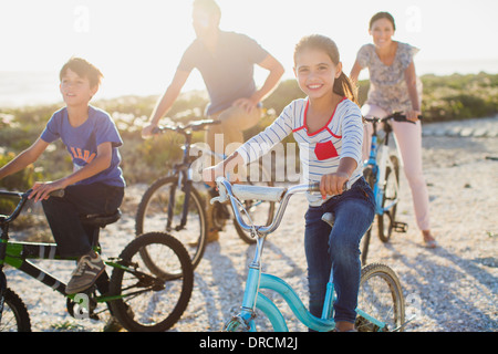 Family riding bicycles on sunny beach - Stock Photo