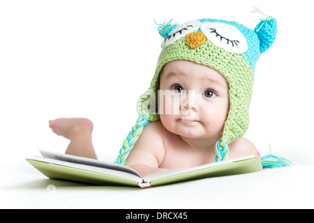 baby in funny owl knitted hat owl with book on white background - Stock Photo