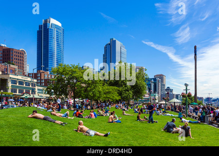 People sunbathing in Victor Steinbrueck Park in front of the downtown skyline, Seattle, Washington, USA - Stock Photo