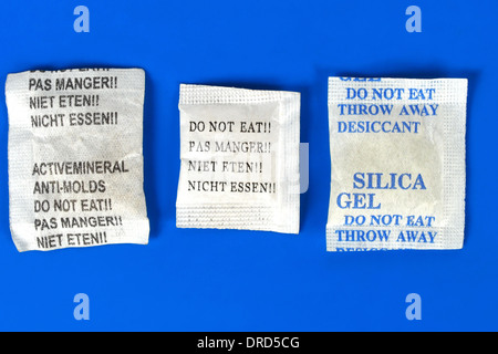 Macro of silica gel bags on blue background - Stock Photo
