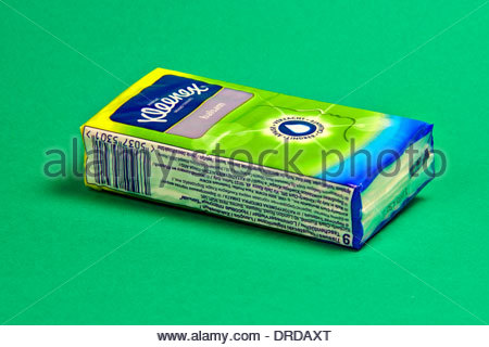 single packet of kleenex paper tissues on a green background - Stock Photo