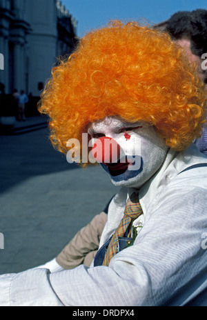 A street mime wearing a curly orange wig takes a break from his silent sidewalk performances for tourists visiting - Stock Photo