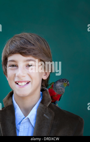 Young boy with pet parrot on shoulder - Stock Photo