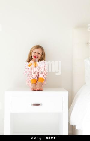 Girl in pajamas sitting on nightstand - Stock Photo