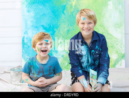 Brothers laughing in front of painting - Stock Photo