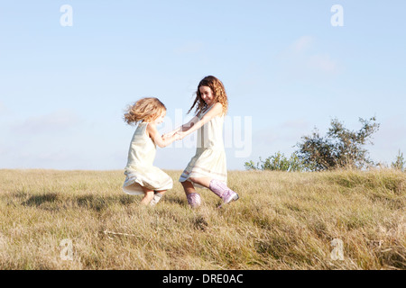 Sisters in dresses standing in field - Stock Photo