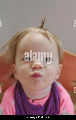 Baby with food all over her face - Stock Photo