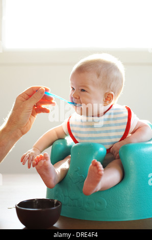 Baby being spoon fed - Stock Photo