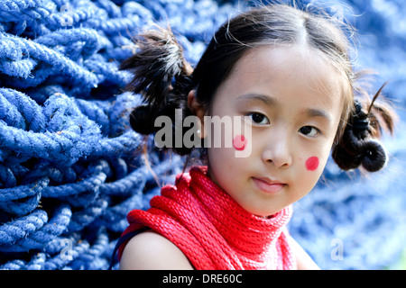 Asian girl in front of blue rope wall - Stock Photo